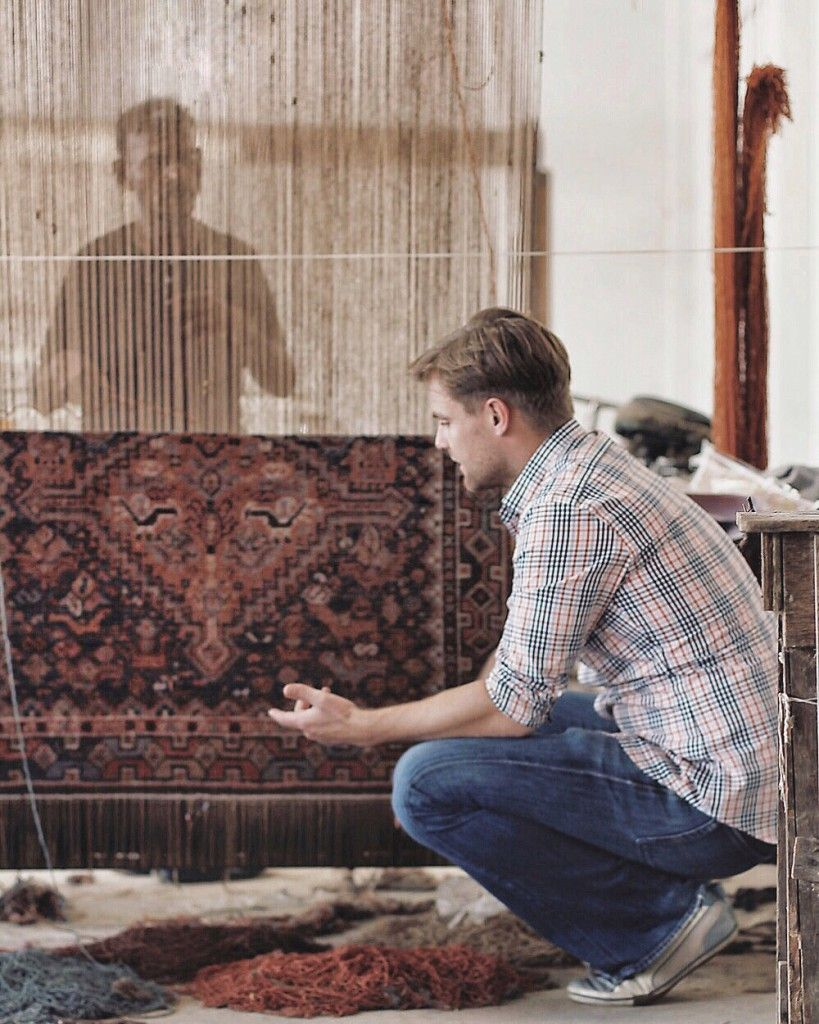 Alex in India looking at a handmade rug